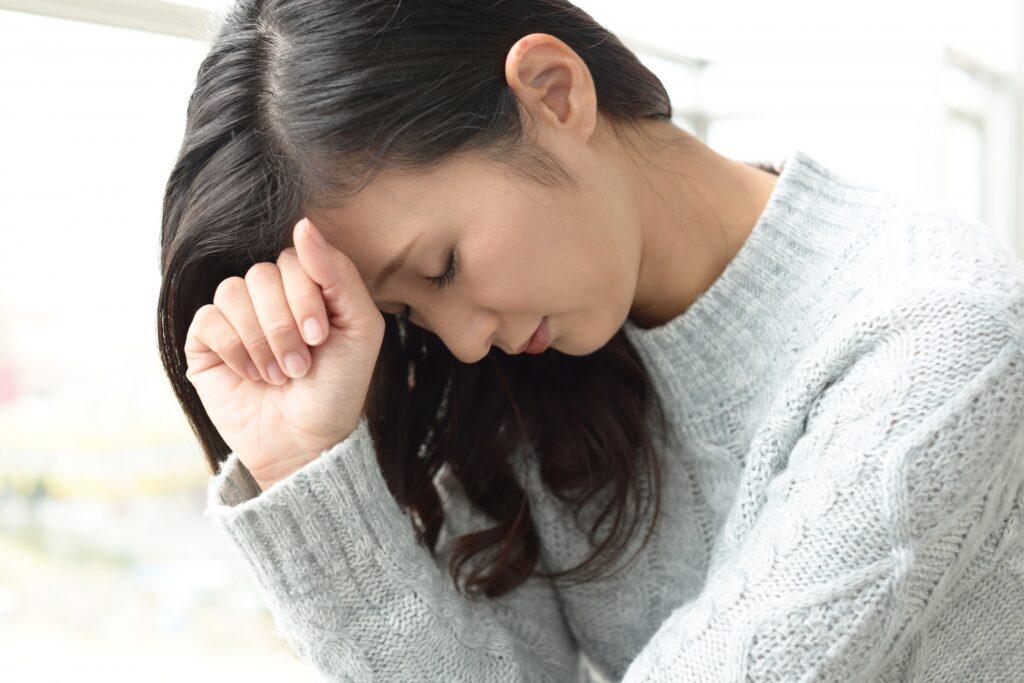 首の痛みに悩む女性